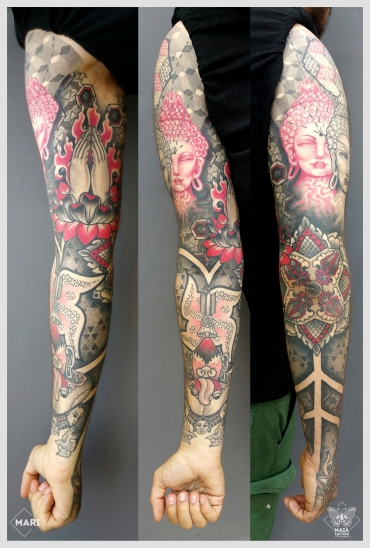 Fotografia di un braccio e mano tatuati in stile ornamentale e dotwork, raffiguranti, tre Buddha, mani in preghiera, svastica, fiore di loto e demoni, con sfondi a texture e pattern geometrici. Il tatuaggio è stato eseguito da Marianna Bevilacqua