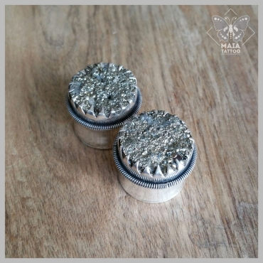 Fotografia di due plugs in argento con incastonate pietre in ematite grezze, realizzati a mano da Mysteeco Unique Body Jewellery, disponibili presso il Maia Tattoo di Cornaredo Milano