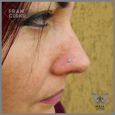 Fotografia di un Piercing alla narice (nostril) con gioiello in opale bianco, eseguito da Francesco Deschino allo studio Maia Tattoo di Milano Cornaredo