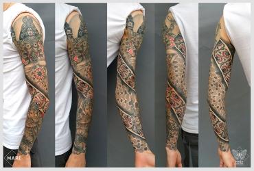 Fotografia di un tatuaggio stile ornamentale su braccio, con elementi figurativi quali Ganesh e dea Kali, con sfondo a texture e pattern eseguito da Marianna Bevilacqua nello studio Maia Tattoo, a Cornaredo, Milano.