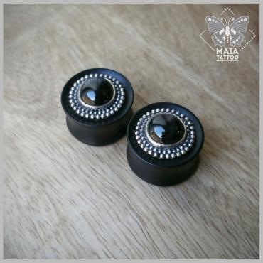 Fotografia di due plugs in legno di ebano con inserti in argento e pietra Diopside nera, realizzati a mano da Mysteeco Unique Body Jewellery, disponibili presso il Maia Tattoo di Milano Cornaredo