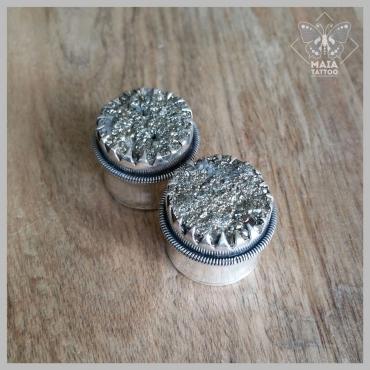 Fotografia di due plugs in argento con incastonate pietre in ematite grezze, realizzati a mano da Mysteeco Unique Body Jewellery, disponibili presso il Maia Tattoo di Cornaredo Milano