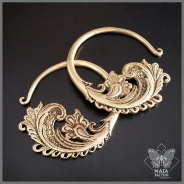 Fotografia di pesi per orecchie in ottone con lavorazione ornamentale, decorativa.  Maia Tattoo Cornaredo - Gioielleria - Plugs - Diablo Organics - Pesi Oro