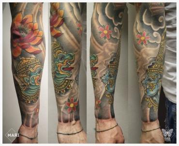 Tatuaggio in stile giapponese ornamentale su avambraccio, raffigurante guardiani induisti e un fiore di loto su gomito, eseguito da Marianna Bevilaqua