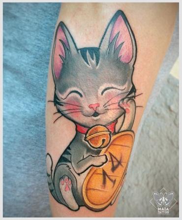 Fotografia di un avambraccio maschile con un tatuaggio di un maneki neko, anche noto come
