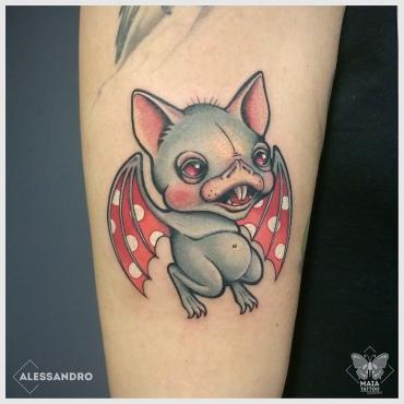Fotografia di un braccio femminile con tatuato un pipistrello con ali a pois colorato, in stile new school/cartoon, realizzato da Alessandro Paparella presso lo studio Maia tattoo di cornaredo MIlano