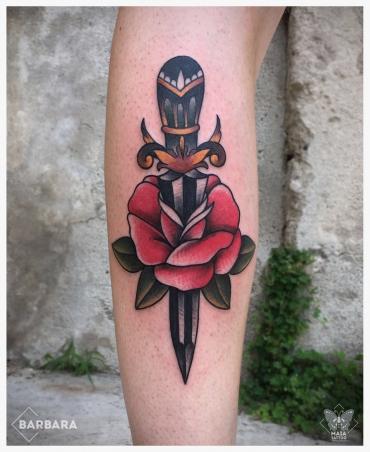Fotografia di un polpaccio di uomo con Tatuaggio di un pugnale con una rosa in stile tradizionale a colori , eseguito da Barbara Schena presso lo studio Maia Tattoo di