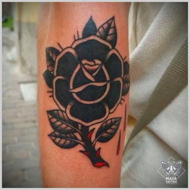 Fotografia di un avambraccio di uomo con tatuata una rosa nera in stile tradizionale, eseguita da Alessandro Paparella nello studio Maia Tattoo di Milano Cornaredo