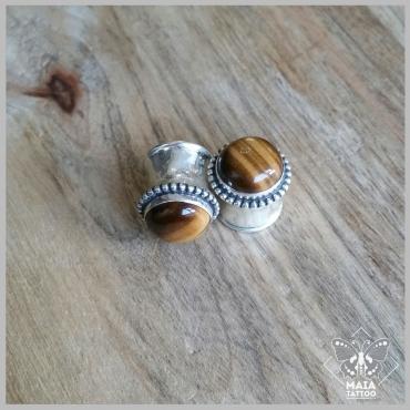 Fotografia di due Dilatazioni double flair in argento con inserimento di pietra tiger eye, realizzati a mano da Meesteco, disponibili presso Maia Tattoo Milano Cornaredo