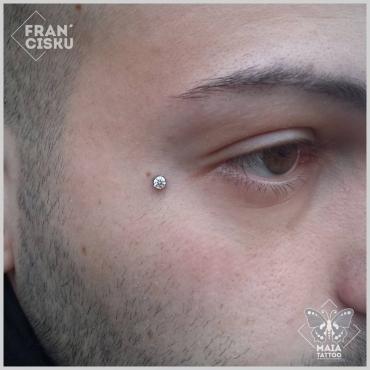 Fotografia di un viso di uomo con microdermal su zigomo con zircone bianco, eseguito da Francesco Deschino presso il Maia Tattoo di Milano Cornaredo